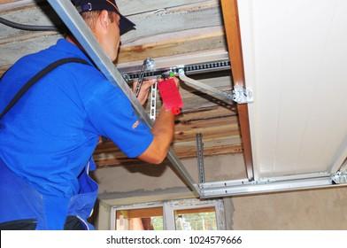 KYIV, UKRAINE - February, 14, 2018: Worker installing garage door opener system. Garage door repair.