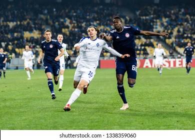 Kyiv, Ukraine - February 22, 2019: Mykola Shaparenko of Dynamo Kyiv fighting for the ball with Papa Abou Cisse of Olympiakos during UEFA Europa League match at NSC Olimpiyskiy stadium.