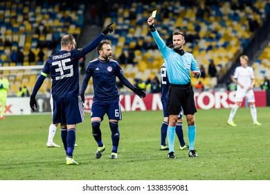 Kyiv, Ukraine - February 22, 2019: Vasilis Torosidis of Olympiacos FC gets yellow card in UEFA Europa League match against Dynamo Kyiv at NSC Olympic stadium.