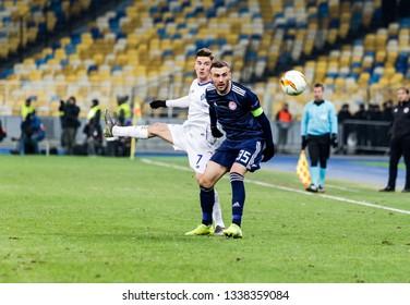 Kyiv, Ukraine - February 22, 2019: Benjamin Verbic of Dynamo Kyiv fighting for the ball with Vasilis Torosidis of Olympiakos during UEFA Europa League match at NSC Olimpiyskiy stadium.