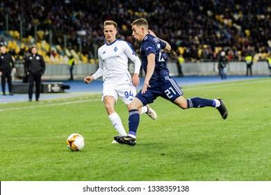 Kyiv, Ukraine - February 22, 2019: Tomasz Kedziora of Dynamo Kyiv fighting for the ball with Konstantinos Tsimikas of Olympiakos during UEFA Europa League match at NSC Olimpiyskiy stadium.