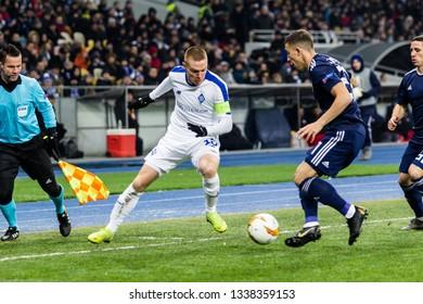 Kyiv, Ukraine - February 22, 2019: Viktor Tsyhankov of Dynamo Kyiv fighting for the ball with Konstantinos Tsimikas of Olympiakos during UEFA Europa League match at NSC Olimpiyskiy stadium.