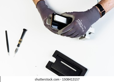 KYIV, UKRAINE - FEBRUARY 27 2019: Man Repair Mobile Phone Broken Display Top Down View. Hands in Glove Dismantle Smartphone Crack Glass Cover on White Background. Cellphone Holder Tool Overhead