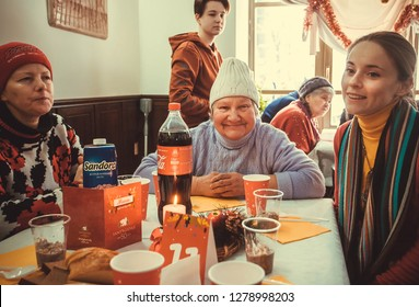 KYIV, UKRAINE - JAN 7: Group of happy poor women meeting for lunch at the Christmas charity dinner for homeless on January, 2018, in Kiev, Ukraine. About 100,000 adults are the homeless in Ukraine