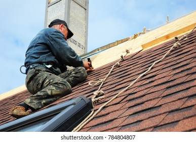 KYIV, Ukraine - January 02, 2018: Roofer laying asphalt shingles on new roof.  Roofer with protection rope, safety kit on the house roof installing, repair asphalt shingles. Roofing construction.