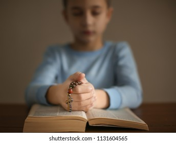KYIV, UKRAINE - JANUARY 03, 2018: Little boy praying over Bible at table
