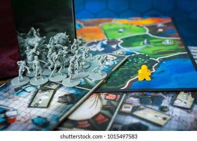 Kyiv, Ukraine - January 13 2018: Board game concept- many board game field, meeple figures run away from zombi figures