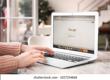 KYIV, UKRAINE - JANUARY 15, 2018: Woman using Apple Macbook Air with Google search page on screen at table in cafe