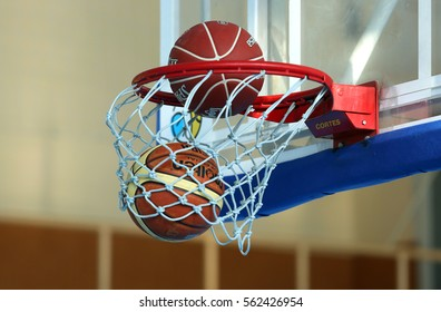 KYIV, UKRAINE - JANUARY 23, 2017: Official Molten and Spalding basketball balls hits the Cortes hoop at the same time. Blurred gym at background.