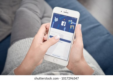 Kyiv, Ukraine - January 24, 2018: Woman start to use Facebook app on Apple  iPhone 8 Plus at home. Facebook is a social media online service for microblogging and networking.