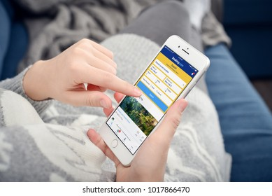Kyiv, Ukraine - January 24, 2018: Woman using Booking.com app on  Apple iPhone 8 plus at home. Booking.com is a most popular hotel booking system in Europe.