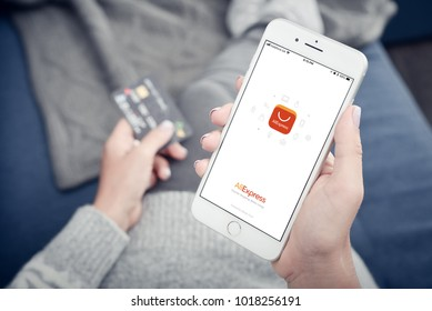Kyiv, Ukraine - January 24, 2018: Woman holding Apple Iphone 8 plus with loading Aliexpress mobile app at home closeup.