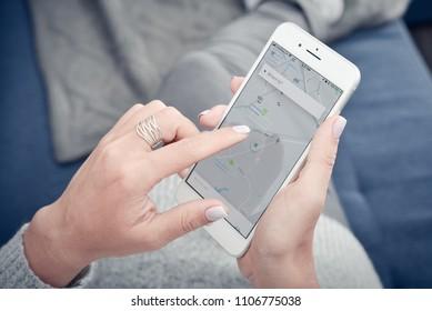 Kyiv, Ukraine - January 24, 2018: Woman using Uber app on Apple iPhone 8 plus at home. Uber is smartphone app-based transportation network.