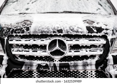 Kyiv, Ukraine - January 28th, 2020:  car wash, logo Mercedes  company badge in front of the black car.