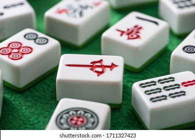 KYIV, UKRAINE - JANUARY 30, 2019: selective focus of white mahjong game tiles with signs and symbols on green velour surface