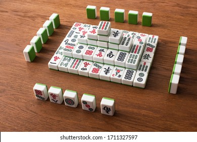 KYIV, UKRAINE - JANUARY 30, 2019: rows and pyramid made of mahjong game tiles on wooden table