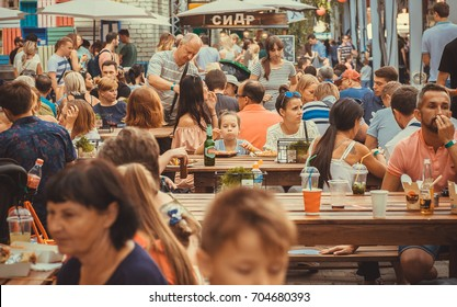 KYIV, UKRAINE - JUL 23: Crowd of hungry people eating meals around tables outdoor during Street Food Festival on July 23, 2016. Kiev is the 8th most populous city in Europe.