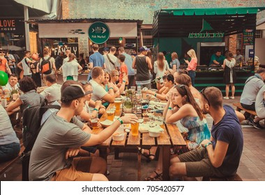 KYIV, UKRAINE - JUL 23: Friendly party with crowd of  people eating at table during outdoor Street Food Festival on July 23, 2016. Kiev is the 8th most populous city in Europe.