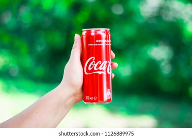 KYIV, UKRAINE - JULY 04, 2018: Holding a bottle of Coca-Cola soft drink.Coca-Cola Company is the leading manufacturer of soda drinks in the world. Illustrative editorial photo.