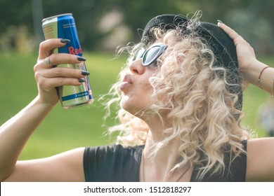 KYIV, UKRAINE - JULY 04, 2019: Red Bull is an energy drink sold by Austrian company Red Bull GmbH, created in 1987. beautiful blonde woman drinks red bull in the park.