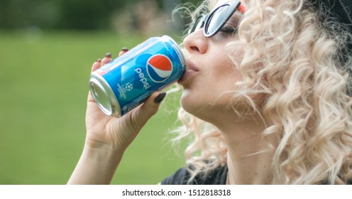 KYIV, UKRAINE - JULY 04, 2019:  Pepsi is carbonated soft drink produced by PepsiCo. Pepsi was created and developed in 1893. beautiful blonde woman drinks pepsi in the park