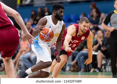 KYIV, UKRAINE - JULY 1, 2018: Eugene Jeter runs and dribble going over tough defense by Janis Strelnieks. FIBA World Cup 2019 European Qualifiers match Ukraine-Latvia