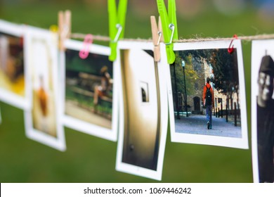 Kyiv, Ukraine - July 15, 2017: Instant photos with images of different people hanging on a rope outside with clothespins.