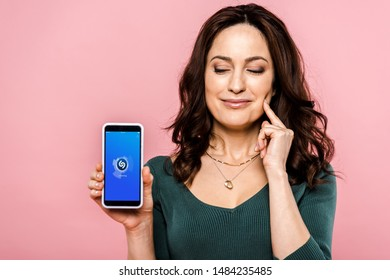 KYIV, UKRAINE - JULY 17, 2019: happy woman holding smartphone with shazam app on screen isolated on pink