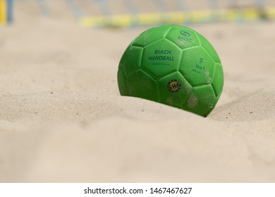 KYIV, UKRAINE - JULY 19, 2019: Beach handball Ukrainian Cup 2019. Official EHF beach handball ball. Green color beach handball ball beautiful close-up view on the sand background on a sunny day.