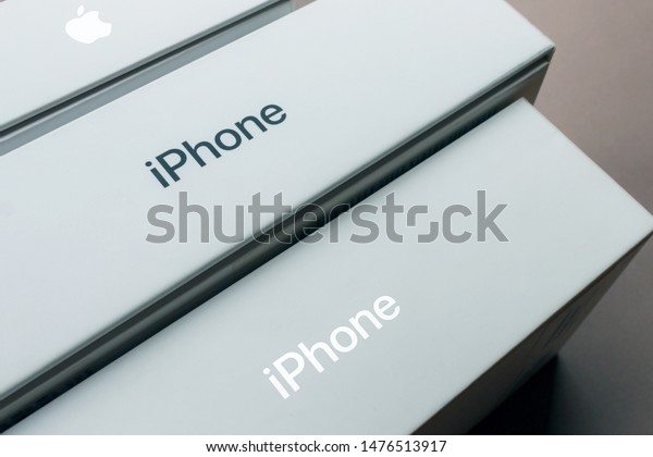 KYIV, UKRAINE - July 30, 2019: gray iphone logo on a new apple retail boxes close-up, brown background. a row with boxes with iphone хs max and air pods