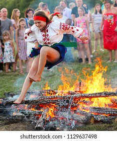 KYIV, UKRAINE - JULY 6, 2018: Young girl in national clothing jumps over the  bonfire during the traditional Slavic celebration of Ivana Kupala holiday in Pirogovo open-air ukrainian folk museum