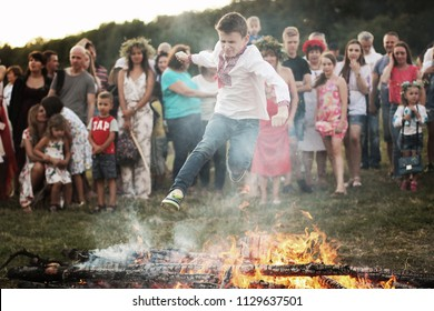 KYIV, UKRAINE - JULY 6, 2018: Young boy jumps over the flames of bonfire during the traditional Slavic celebration of Ivana Kupala holiday in Pirogovo open-air ukrainian folk museum