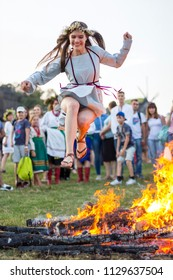 KYIV, UKRAINE - JULY 6, 2018: Young girl jumps over the flames of bonfire during the traditional Slavic celebration of Ivana Kupala holiday in Pirogovo open-air ukrainian folk museum