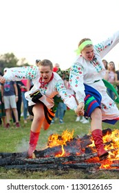 KYIV, UKRAINE - JULY 6, 2018: Young people jump over the flames of bonfire during the traditional Slavic celebration of Ivana Kupala holiday in Pirogovo open-air ukrainian folk museum