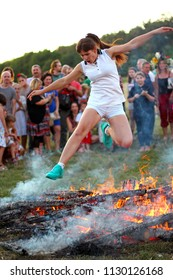 KYIV, UKRAINE - JULY 6, 2018: Young woman jumps over the flames of bonfire during the traditional Slavic celebration of Ivana Kupala holiday in Pirogovo open-air ukrainian folk museum