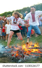 KYIV, UKRAINE - JULY 6, 2018: People jump over the flames of bonfire during the traditional Slavic celebration of Ivana Kupala holiday in Pirogovo open-air ukrainian folk museum