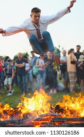KYIV, UKRAINE - JULY 6, 2018: Young man jumps over the flames of bonfire during the traditional Slavic celebration of Ivana Kupala holiday in Pirogovo open-air ukrainian folk museum