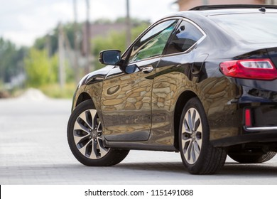 KYIV, UKRAINE - July 9, 2018: Back view of modern black shiny Honda car parked on paved sunny street on blurred summer suburb quiet street background. Transportation, speed, elegance, luxury concept.