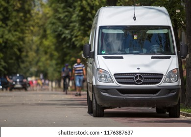 KYIV, UKRAINE - July 9, 2018: White passenger medium size commercial German luxury Mercedes minibus van parked on city street with blurred silhouettes of pedestrians and moving car under green trees.