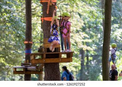 KYIV, UKRAINE - July 9, 2018: Children having fun on rope way in recreation park. Cute young girl in safety helmet hangs on harness attached with carbine to rope on green sunny bokeh background.