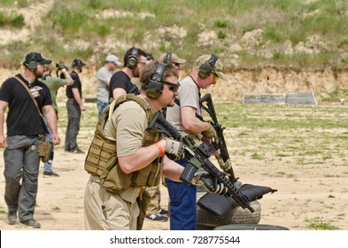"KYIV, UKRAINE - JUNE 17 2017: The civil men are trained by the coach at the outdoor shooting range during ""Open Gun Day"". KYIV, UKRAINE - JUNE 17 2017."