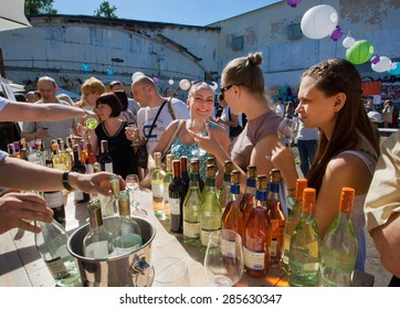 KYIV, UKRAINE - JUNE 6, 2015: Women tasting red and white wine in outdoor bar of summer Kiev Food & Wine Festival on June 20, 2014. Kiev is 8th largest city in Europe with populat. of 2,900,000