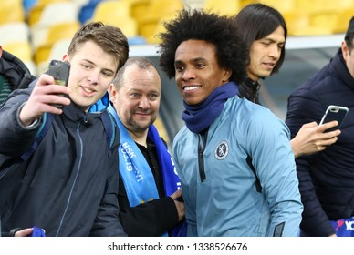 KYIV, UKRAINE - MARCH 13, 2019: Football fan makes selfie portrait with player Willian of Chelsea during the training session before the UEFA Europa League game against FC Dynamo Kyiv