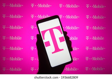 KYIV, UKRAINE - MARCH 15, 2021: In this photo illustration T-Mobile logo of the brand name used by the mobile communications subsidiaries of Deutsche Telekom is seen on a mobile phone in a hand.