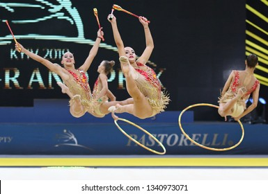 """KYIV, UKRAINE - MARCH 16, 2019: Team of RUSSIA performs with 3 Hoops and 2 Clubs during Group Competition of Rhythmic Gymnastics Grand Prix """"Deriugina Cup"""" in Palace of Sports in Kyiv, Ukraine"""