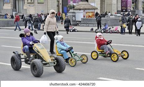 KYIV, UKRAINE - MARCH 17, 2013: Folk celebrating the Shrovetide on Kreschatik street. Three Children on childish cars.