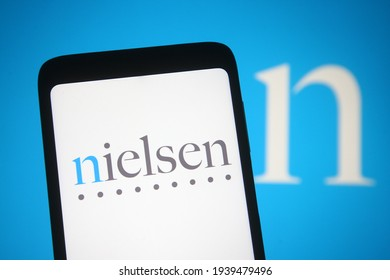 KYIV, UKRAINE - MARCH 19, 2021: In this photo illustration Nielsen Holdings PLC is an American, UK-domiciled, information, data and market measurement firm is seen on a mobile phone and a computer scr