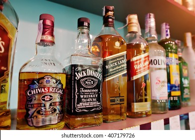KYIV, UKRAINE - MARCH 25, 2016: Various alcoholic beverages bottles in the bar. Chivas Regal, Jack Daniel's and Black Label at center