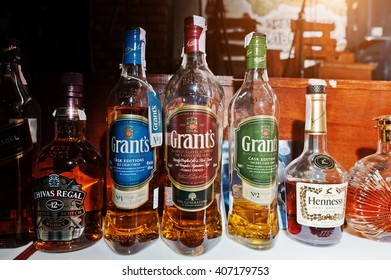 KYIV, UKRAINE - MARCH 25, 2016: Various alcoholic beverages bottles in the bar. Grants scotch whiskey at center