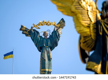 Kyiv, Ukraine - March 25, 2018: Statue of Berehynia on the top of Independence Monument on the Maidan Nezalezhnosti in Kiev, Ukraine.( In the foreground statue of Archangel Michael )